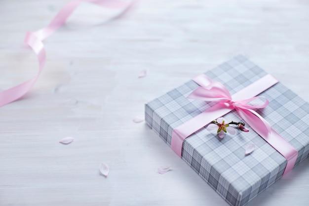 Caixa de presente romântica com fita rosa sobre fundo claro de madeira