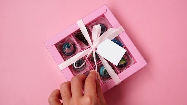 Caixa de presente rosa com bombons de chocolate com chocolates artesanais na cor rosa