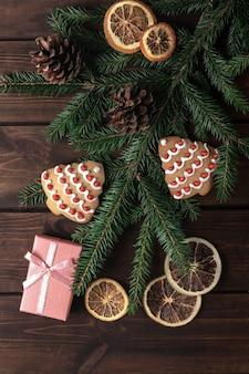 Caixa de presente rosa com cones, ramos de abeto, biscoitos em forma de árvore de natal e fatias secas de frutas cítricas