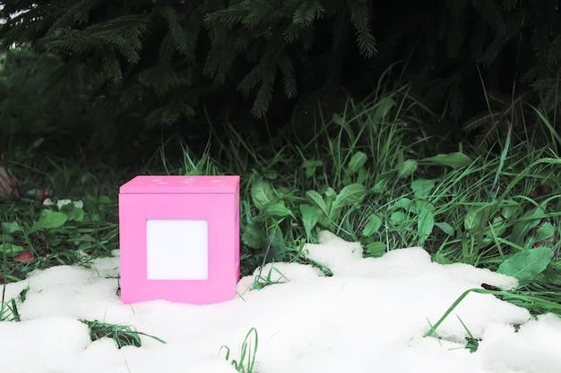 Caixa de presente rosa decorativa sobre neve fresca ao ar livre