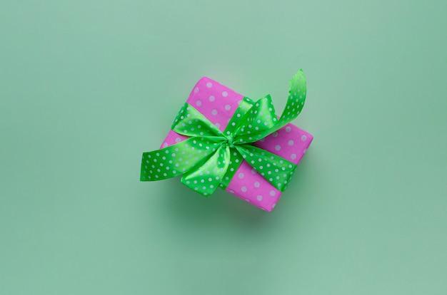 Caixa de presente rosa ou presente com fita sobre fundo verde pastel