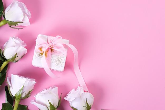 Caixa de presente rosa rosa e branco com fita rosa em fundo rosa