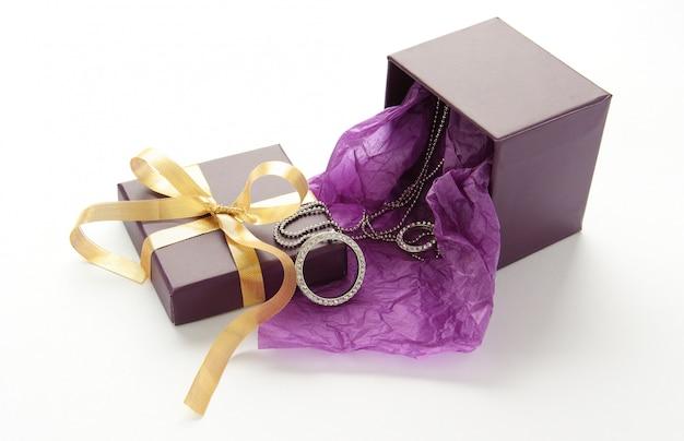 Caixa de presente roxa com jóias e fita amarela sobre branco