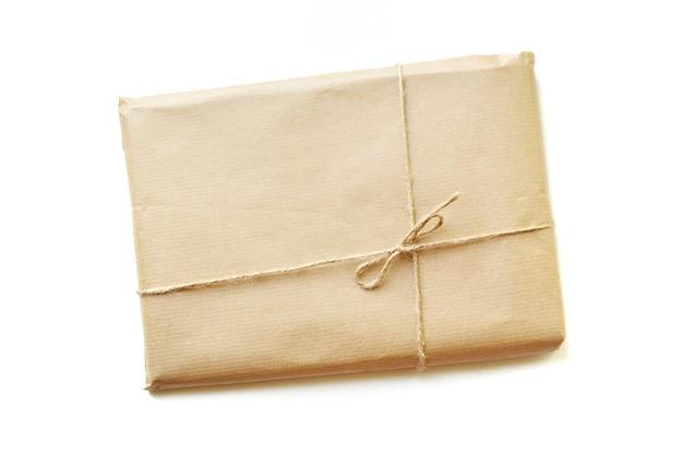 Caixa de presente rústica embalada em papel pardo amarrado por barbante com espaço em branco no fundo branco com espaço para texto