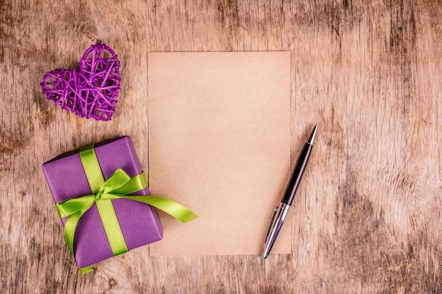 Caixa de presente, saudação coração e folha de papel em branco.