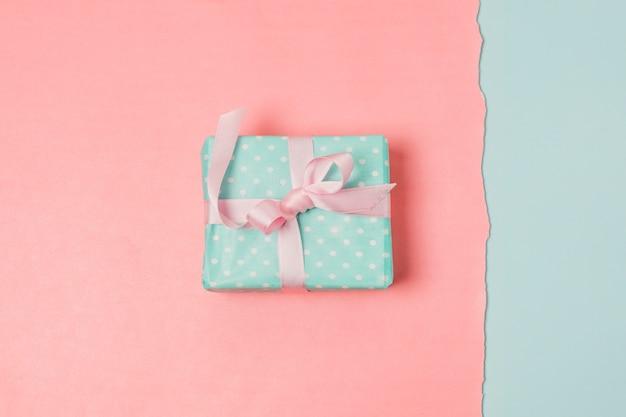 Caixa de presente sobre pano de fundo azul e pêssego