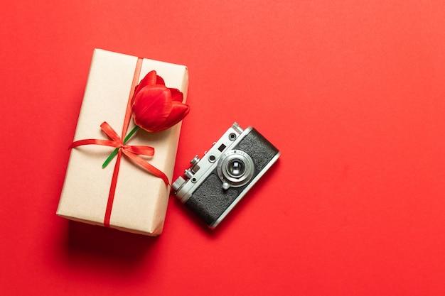 Caixa de presente surpresa com uma fita vermelha e uma tulipa sobre um fundo vermelho, uma câmera de foto modelo antigo