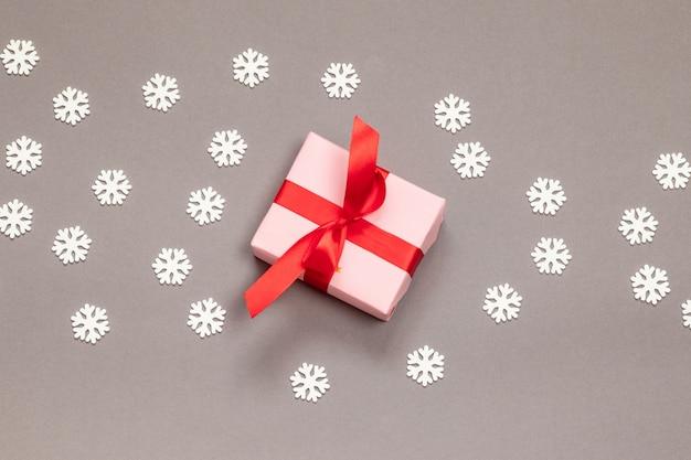 Caixa de presente surpresa de papel com fita vermelha e flocos de neve brancos em uma vista cinza, superior. ano novo. cartão de feliz natal.