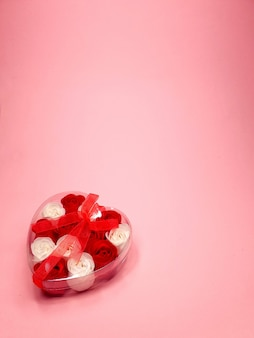 Caixa de presente transparente com uma fita em forma de coração com pequenas flores sobre fundo rosa suave, copie o espaço. conceito de design de dia dos namorados.
