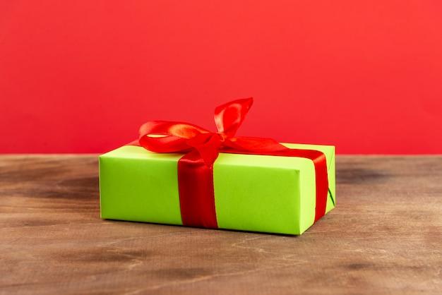 Caixa de presente verde com fita vermelha em uma mesa de madeira e fundo vermelho