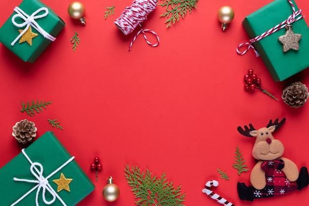 Caixa de presente verde de natal com ramos de abeto, pinhas, bagas vermelhas sobre fundo vermelho.