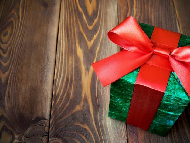 Caixa de presente verde na placa de madeira. copie o espaço. conceito de férias