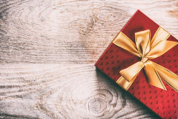 Caixa de presente vermelha amarrada com fita de seda dourada