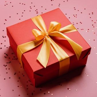 Caixa de presente vermelha amarrada com uma fita dourada. fita amarrada com um laço em uma caixa.