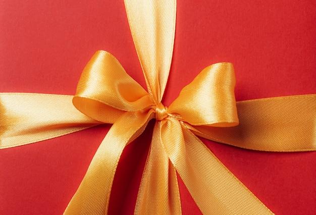 Caixa de presente vermelha amarrada com uma fita dourada