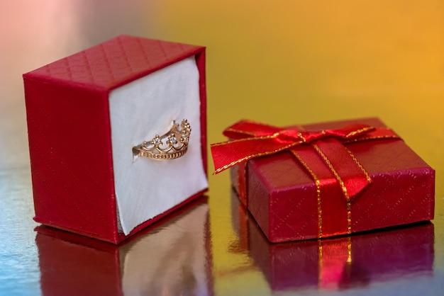 Caixa de presente vermelha com anel dourado em forma de coroa
