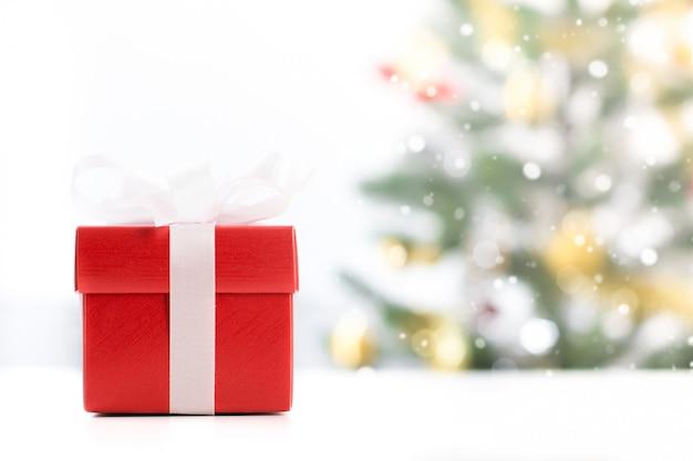 Caixa de presente vermelha com blur árvore de natal no fundo