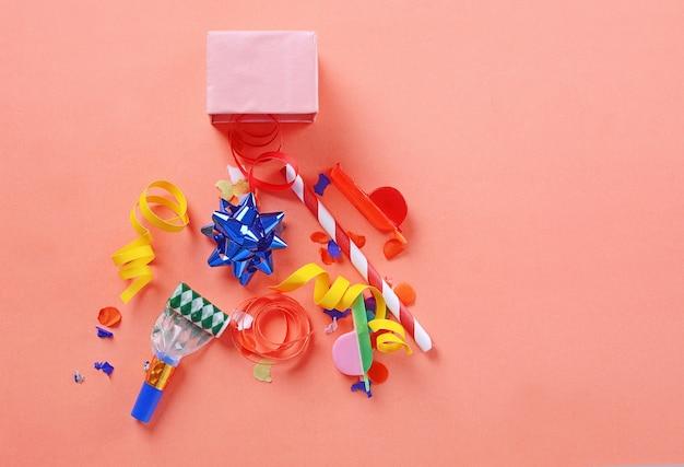 Caixa de presente vermelha com confetes de festa, flâmulas e noisemakers