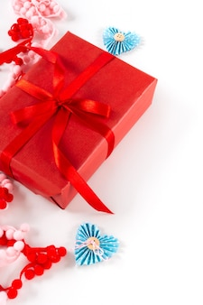 Caixa de presente vermelha com coração e laço em fundo branco. dia dos namorados 14 de fevereiro conceito de embalagem.