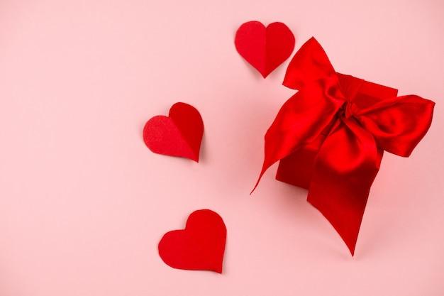 Caixa de presente vermelha com fita de cetim vermelha amarrado arco e papel corações rosa