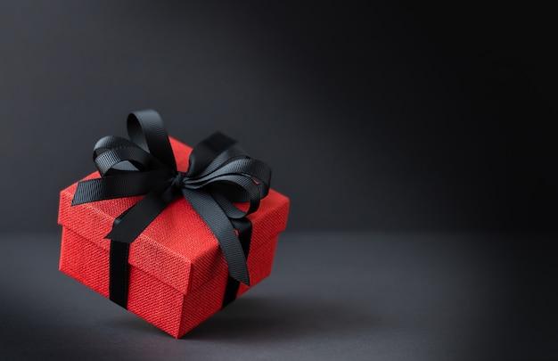 Caixa de presente vermelha com fita preta em fundo preto