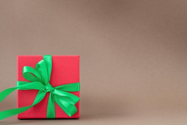 Caixa de presente vermelha com fita verde em fundo marrom