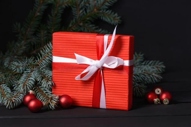 Caixa de presente vermelha com fundo de árvore do abeto e bolas de vidro