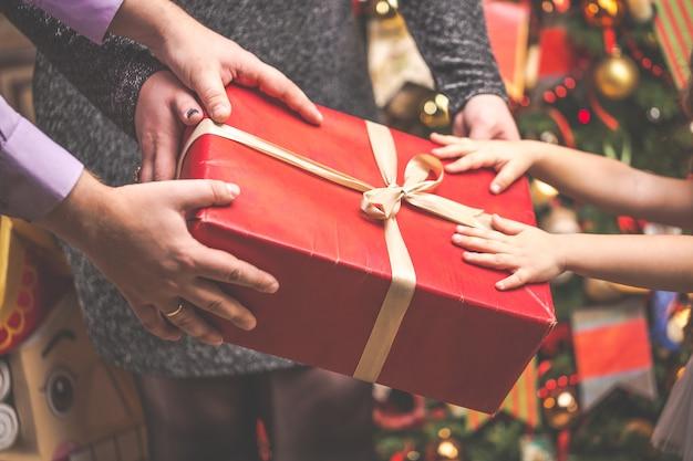 Caixa de presente vermelha com todas as mãos de família contra a árvore de natal.