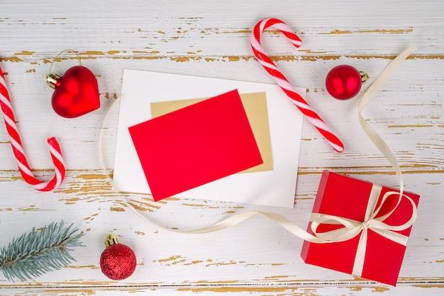 Caixa de presente vermelha com um brinquedo de natal em forma de coração, ramos de abeto, doces de natal, guirlanda e cartão de fundo