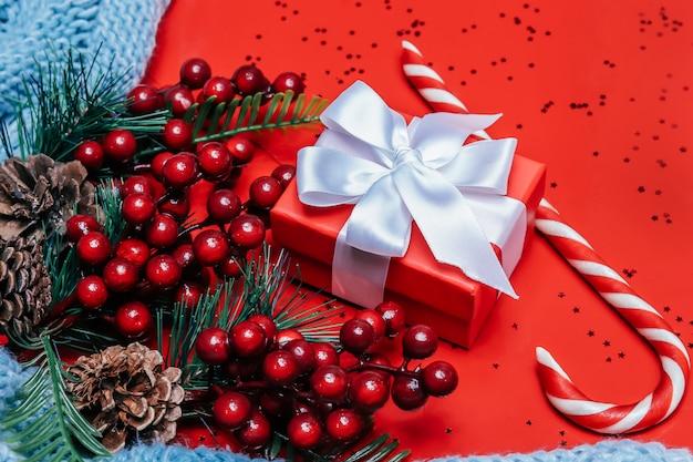 Caixa de presente vermelha com um laço branco com ramos de doces e abeto