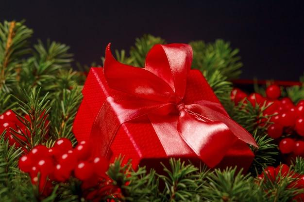 Caixa de presente vermelha de natal com laço de cetim decorado com frutas vermelhas.
