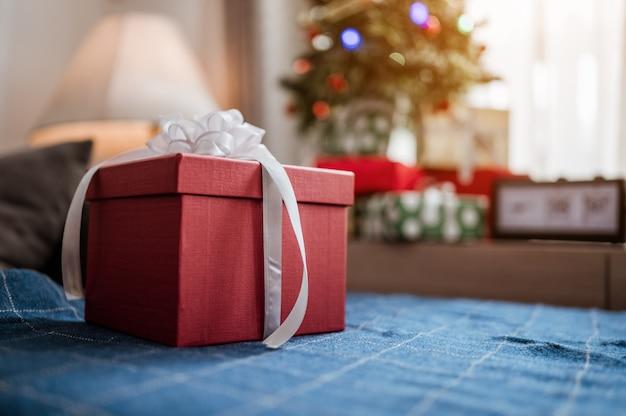 Caixa de presente vermelha de natal e fundo de natal com árvore de natal na mesa de madeira. ornamentos vermelhos, dourados e prateados. comemore o natal em casa.
