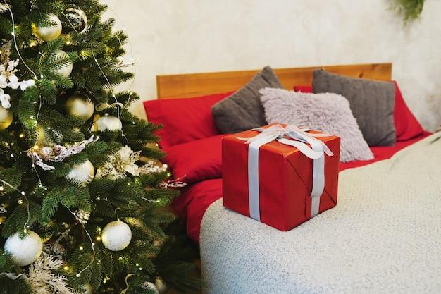 Caixa de presente vermelha de natal na cama perto da árvore em casa