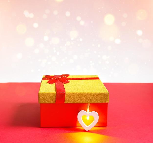 Caixa de presente vermelha e coração com uma lâmpada brilhante dentro