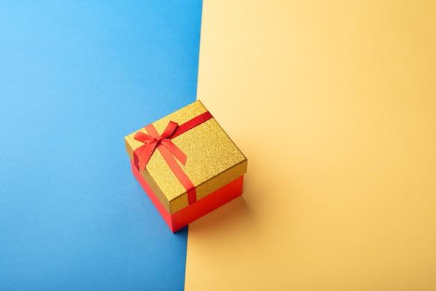 Caixa de presente vermelha e dourada com uma fita em um fundo brilhante de duas cores