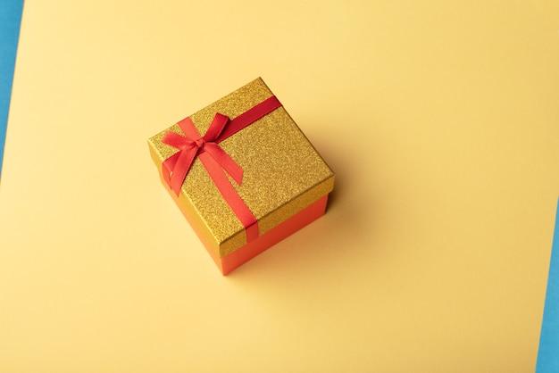 Caixa de presente vermelha e dourada com uma fita vermelha em um fundo amarelo