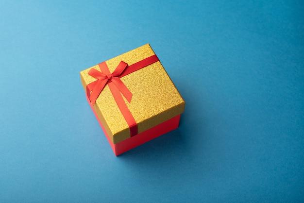 Caixa de presente vermelha e dourada com uma fita vermelha em um fundo azul claro
