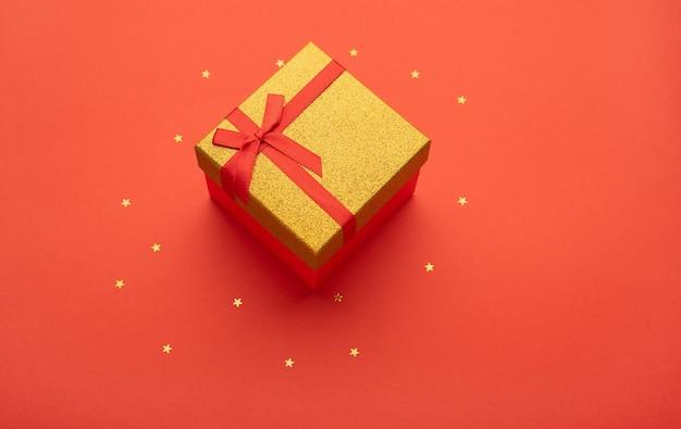 Caixa de presente vermelha e dourada em um fundo vermelho brilhante com estrelas douradas