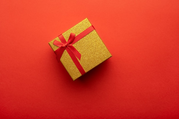 Caixa de presente vermelha e dourada em um fundo vermelho brilhante vista superior plana
