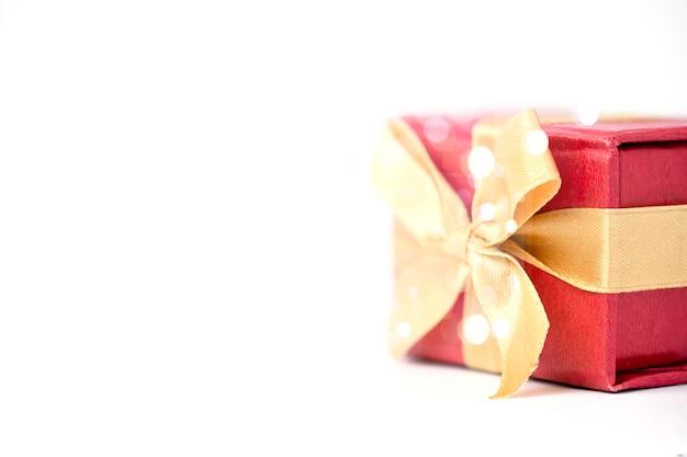 Caixa de presente vermelha e fita dourada sobre fundo branco e bokeh, feliz aniversário e feliz ano novo conceito.