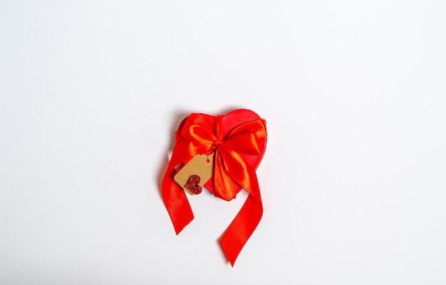 Caixa de presente vermelha em forma de coração com uma fita e uma etiqueta de parabéns