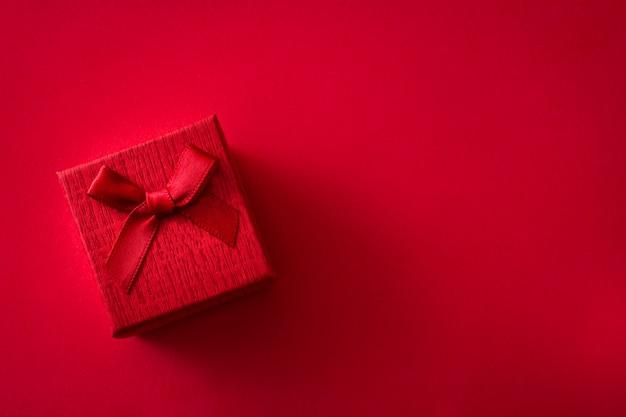 Caixa de presente vermelha em fundo vermelho com espaço de cópia