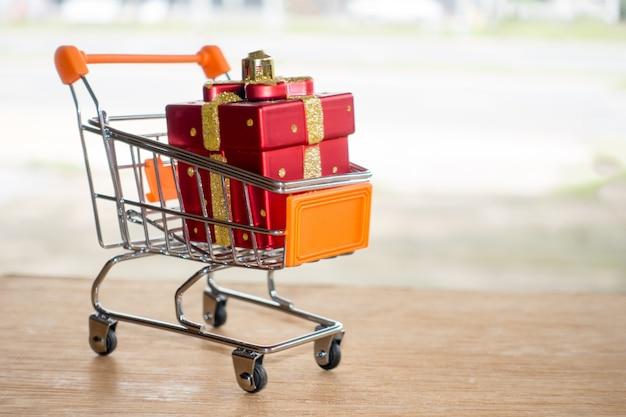 Caixa de presente vermelha em um carrinho de compras na tabela de madeira compra em linha do conceito.