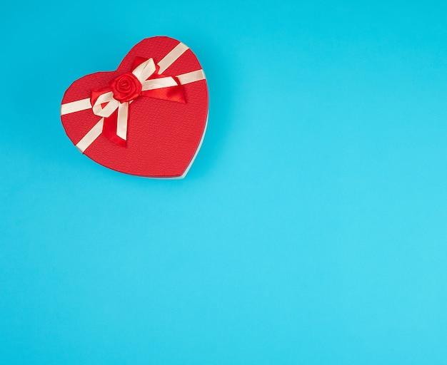 Caixa de presente vermelha na forma de um coração com um laço em um fundo azul