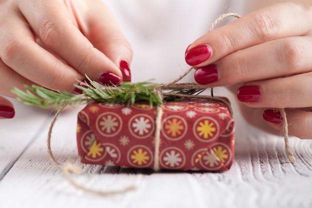 Caixa de presente vermelha nas mãos femininas