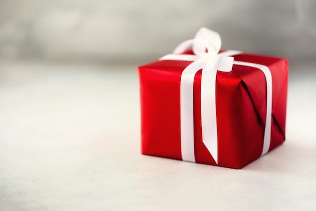 Caixa de presente vermelha no concreto cinzento, espaço da cópia. natal, ano novo, festa de aniversário, dia dos namorados, mãe e mulher dia conceito.