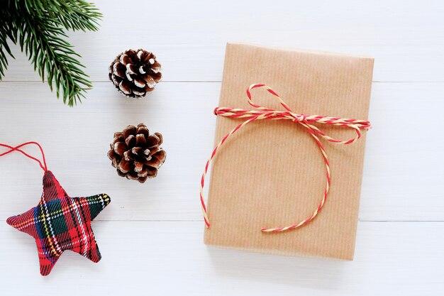Caixa de presente vintage marrom e ornamento em fundo branco de madeira, cartão de natal
