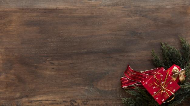 Caixa de presentes e fitas em galhos de coníferas