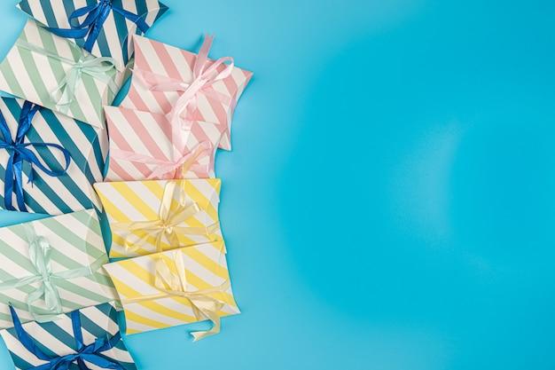 Caixa de presentes em várias cores, colocada à esquerda da foto em um azul