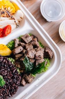 Caixa de refeição de comida limpa: carne grelhada em cubos, servida com arroz, brócolis, milho, cogumelo a